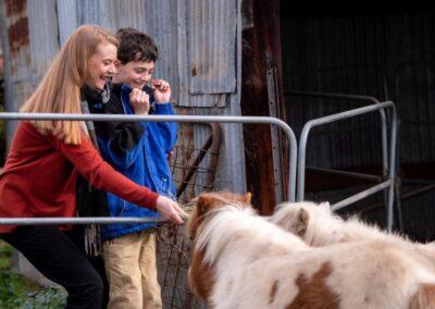 Simone feeding a pony with Will