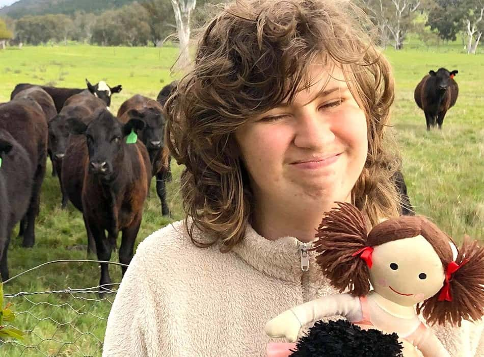 child in the field with cows